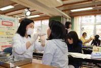 学校で行われている歯科検診。歯垢や歯肉が気になる子どもには、終了時に「歯磨き頑張ろう」「仕上げ磨きをしてもらったほうがいいよ」などと歯科医が声をかけることも=埼玉県朝霞市の市立第八小で