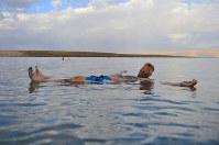 両手を広げて湖面に浮いてみせる男性。どんな「金づち」でも浮くほど塩分濃度が高い=イスラエルの死海で2016年3月、隅俊之撮影