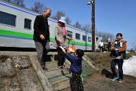 午前9時28分に到着した「最終列車」の乗客に手作りのカードを渡す園児。連休前には太鼓演奏も披露される予定