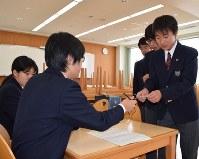 生徒会役員の生徒から組み体操の賛否を投票する模擬投票用紙を受け取る生徒たち=東京都豊島区の区立明豊中学校で2016年4月19日午後1時30分、高木香奈撮影