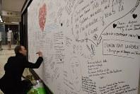 再開したばかりの地下鉄マールベーク駅構内で、犠牲者を悼む言葉をパネルに書き込む男性=ブリュッセルで2016年4月25日午前9時21分、八田浩輔撮影