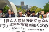 チェルノブイリデーに合わせ慰霊碑前で座り込む参加者たち=広島市中区の平和記念公園で、竹内麻子撮影