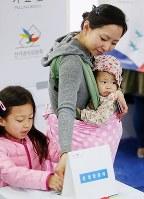 韓国の総選挙で投票する女性=ソウルで13日、聯合・共同