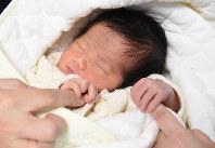 細貝さん夫婦の指をギュッと握る男児。「信頼関係があってお互いに思いやることができればそれが『家族』です」と夫の聡さんは言う=茨城県土浦市で2016年3月24日、内藤絵美撮影