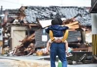 長女ひよりちゃんをおんぶする崎川圭太さん。おしりを支える両手に力を込めた=熊本県益城町で2016年4月27日、山崎一輝撮影