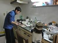 育児休暇中に夕食の準備をする筆者(左)と長男=甲府市の自宅で3月2日夜、筆者の妻撮影