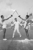 前走者から聖火を受ける五味明大さん(左)=群馬県渋川市で1964年10月5日、本人提供