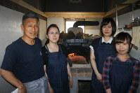 手作りの石窯の前に立つ樋口さん夫婦(左の2人)と長女真美子さん(右奥)、友人の大橋さん(右手前)=新十津川町大和の「石窯カフェ ヤマト」で