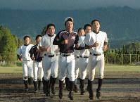 阿蘇の山並みを背にグラウンドでランニングをする阿蘇中央高の選手たち