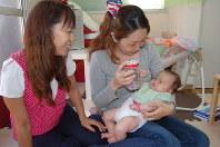 ガラスびんにビーズを入れた手作りのおもちゃを振って琳音ちゃん(右端)をあやす飯田さん(中央)と三浦さん=東京都足立区栗原3の子育てシェアハウスohanaで