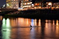 納涼床に明かりがともり、鴨川の水面に色とりどりの夜景が映える=京都市東山区の鴨川東岸から、小松雄介撮影