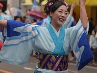 青地に白い波模様が描かれた着物姿で、ハイヤ節に乗って「ヨイサー、ヨイサー」=吉川茂文さん撮影