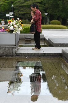 A woman prays in front of the cenotaph in Hiroshima Peace Memorial Park, in Naka Ward, Hiroshima, on May 26, 2016. (Mainichi)