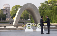 原爆慰霊碑に献花後、安倍晋三首相(左)と握手を交わすオバマ大統領=27日、AP