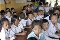 後藤文雄神父らはカンボジアの19カ所に校舎を建てた。村の小学校では子どもたちが目を輝かせ、肩を寄せ合って授業を受けていた=カンボジア・プレイツルテン村で2016年1月