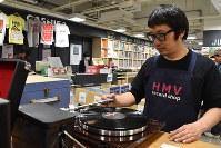 Manager Tomohiro Takeno plays a record at the HMV Record Shop Shibuya in Tokyo's Shibuya Ward. (Mainichi)