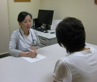 聖路加国際病院相談支援センターで患者の話を聞く橋本久美子さん。患者たちが、仕事をやめないで済む方法を考えるようにしている=東京都中央区で、大和田香織撮影