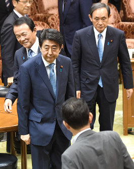 Abe leaves the chamber after bowing to an opposition party member following the adjournment of an upper house Budget Committee meeting on May 13, 2016. Behind Abe are Deputy Prime Minister and Finance Minister Taro Aso, left, and Chief Cabinet Secretary Yoshihide Suga, right. (Mainichi)