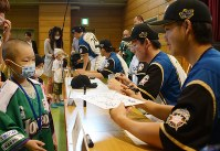 病院内の学校に通う子どもたちにサインを書いて渡す谷口雄也選手(右端)ら=札幌市北区で