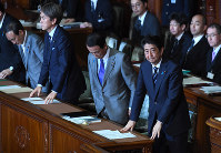Front row from right, Prime Minister Shinzo Abe; Deputy Prime Minister and Finance Minister Taro Aso; Minister in Charge of Economic Revitalization Nobuteru Ishihara, and Chief Cabinet Secretary Yoshihide Suga bow after a no-confidence motion against the Abe Cabinet submitted by four opposition parties was voted down in the House of Representatives, on May 31, 2016. (Mainichi)