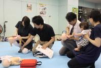 「新米パパママのための応急手当講習会」で人形を使いながら、赤ちゃんが異物を誤飲した際の除去方法について学ぶ両親たち=東京都立川市で