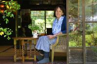 庭の新緑がまぶしい自宅の縁側に座るベニシア・スタンリー・スミスさん=京都市左京区で、小松雄介撮影
