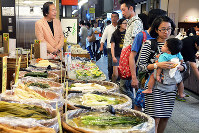 外国人観光客も多く訪れる錦市場で漬物屋をのぞく井上章一さん(左)=京都市中京区で、小松雄介撮影