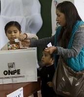 ペルー大統領選の決選投票で投票する女性=首都リマで5日、AP