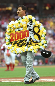 Hanshin Tigers player Kosuke Fukudome shows off a board congratulating him on his 2,000th hit, at Mazda Stadium in Hiroshima on June 25, 2016. (Mainichi)
