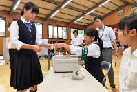 奈良県立橿原高校に期日前投票所が設置され、選挙事務に従事する生徒から投票用紙を受け取る女子生徒(左)=奈良県橿原市で2016年6月27日午後4時7分、大西岳彦撮影