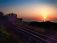 沈む夕日と海沿いを走る山陰線の列車。太陽が長く出ている夏至の前後は、シャッターチャンスに恵まれる=島根県大田市五十猛町で、日本写真家協会会員・船津健一撮影