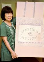 「巡」の字を二十四節気が囲む作品を手に「1年間を表しました」=愛媛県今治市小泉で、松倉展人撮影