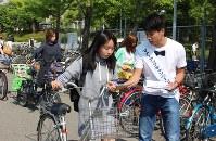自転車保険加入を呼びかけるチラシを配った関西大学の「マナーアップキャンペーン」=大阪府吹田市で