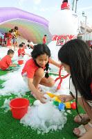 季節外れの雪遊びを楽しむ子供たち=広島市南区のマツダスタジアムで、東久保逸夫撮影