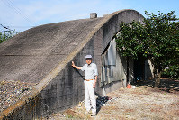 掩体壕の前で保存の必要性を語る杉野富也さん=松山市南吉田町で、黒川優撮影