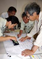 地図やタブレット端末などで状況を地権者(右端)に説明する愛知県職員ら=愛知県犬山市で