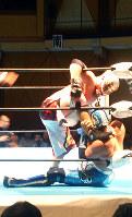 リングコーナーにグルクンマスク(右)を追い詰める首里ジョー。実力派レスラーとして注目されている=大阪市大正区で、金光敏さん撮影