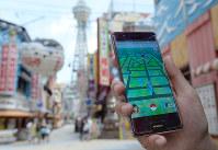 ポケモンGOでモンスターを探す外国人旅行客の画面=大阪市浪速区で2016年7月22日、三浦博之撮影