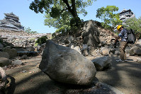 A sloped path leading from the Hohoategomon gate to the main tower of Kumamoto Castle, background right, is seen with stones from a quake-damaged wall, on July 28, 2016. (Mainichi)