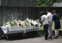 People pray in front of a home for the disabled where 19 people were killed, in Sagamihara, Kanagawa Prefecture, on July 29, 2016. (Mainichi)