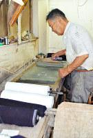 丁寧にのりを塗る森本さん=大阪府柏原市上市2の三共染色で、亀田早苗撮影