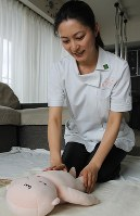 人形でベビーマッサージを実践する萎澤亜希子さん=東京都世田谷区で