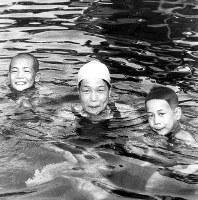 長男の正臣さん(左)と次男の正時さん(右)とともにプールに入る前畑(兵藤)秀子さん=1951年