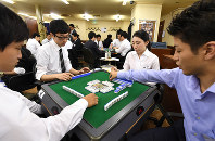 A Startia employee, right, plays mahjong with prospective recruits in Tokyo's Shinjuku Ward in June as part of the recruiting process. (Mainichi)