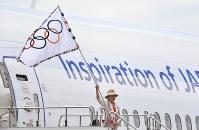 Tokyo Gov. Yuriko Koike waves the Olympic flag at Tokyo's Haneda Airport after returning from Rio de Janeiro, on Aug. 24, 2016. (Mainichi)