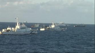 沖縄県・尖閣諸島周辺の領海に侵入した中国公船と漁船に退去を促す海上保安庁の巡視船(左)=海上保安庁提供の動画から