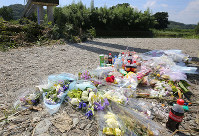 Flowers laid at the riverside in Higashimatsuyama, Saitama Prefecture, where the body of Tsubasa Inoue was found, are seen on Aug. 26, 2016. (Mainichi)