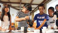ミルを使ってコーヒー豆をひく鎌谷さん=滋賀県甲賀市甲賀町の「レストハウス水車」で、村瀬優子撮影