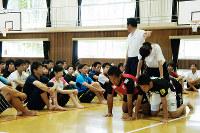 参加した教諭らにピラミッドを組ませて説明する高木校長=大津市昭和町の滋賀大教育学部付属小体育館で、衛藤達生撮影
