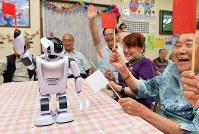 人型コミュニケーションロボット「パルロ」の動きに合わせて、旗あげゲームを楽しむ富山市の「吉田内科クリニック デイサービスあゆみ」の利用者ら=富山市で、大西岳彦撮影